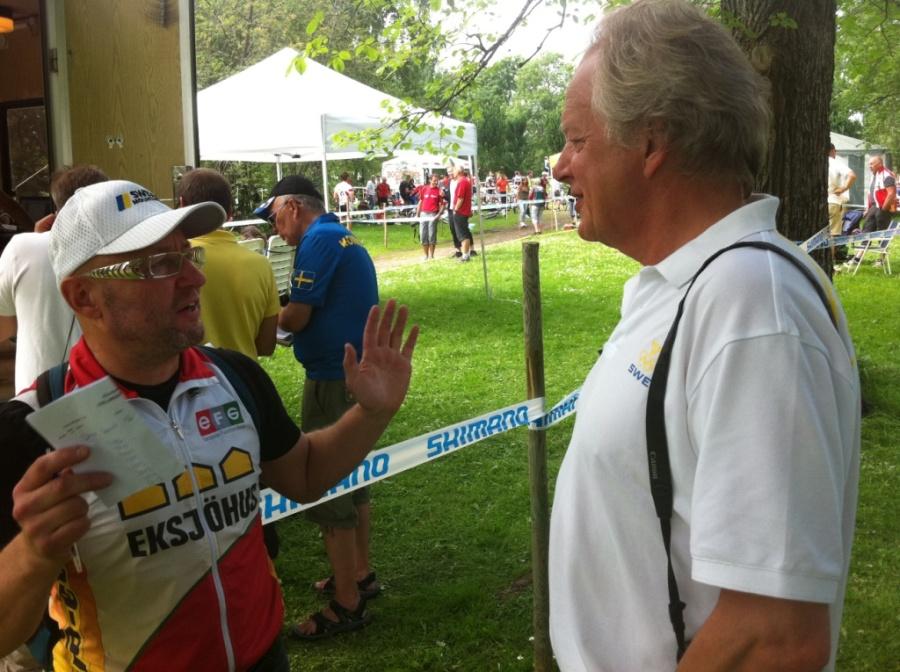 Lasse Strand diskuterar med tävlingsledaren hur länge det ska gå mellan målgång och prisutdelning.