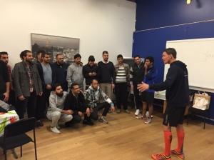 Jonas Colting pratar på en blandning av svenska, engelska och kroppsspråk om löpning på asylboendet i Himle