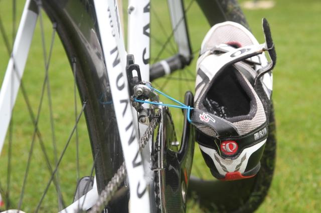 Snabb triathlonväxling T1. Cykelskorna fastsatta på cykeln med gummiband som sedan går sönder.