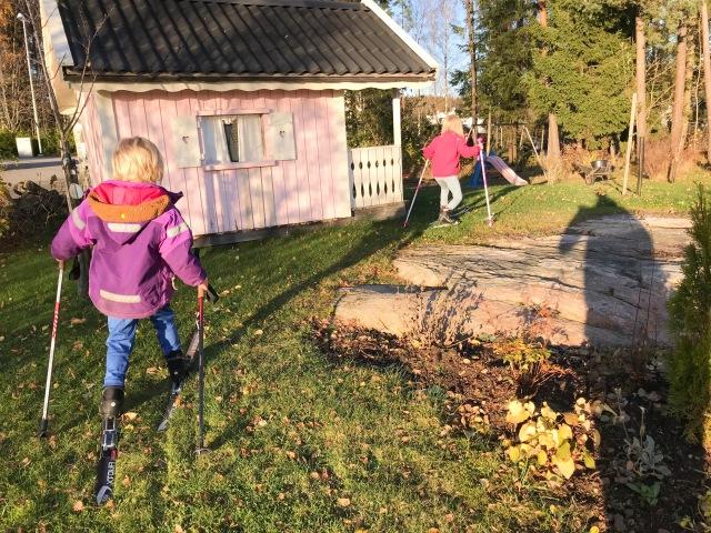 Maj och Astrid åker längdskidor på gräsmattan