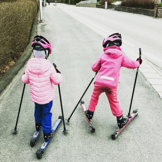 Astrid tjuvskejtade till dagis i morse, medan Maj höll skidorna framåt. Det är inte rullskidor för barn utan vanliga modeller. Stavarna är avbrutna vuxenstavar som jag sågat till och satt på en truga med större diameter för infästningen.