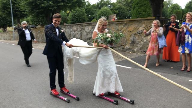 Rickard och Marika Bergengren tolkade på rullskidor efter och mindre bil efter vigseln i kyrkan
