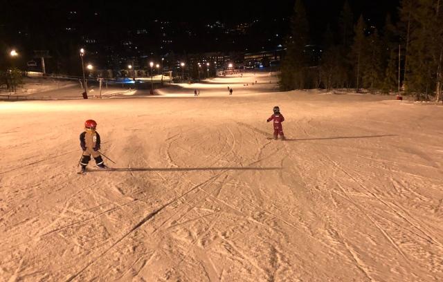 Kvällsskidåkning i Vemdalsskalet. Maj åker baklänges och Astrid åker snowboard.