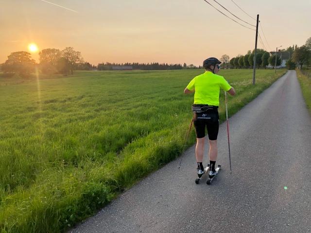 Peter Rosén stakar på rullskidor vid Nordtorp. I solnedgång.