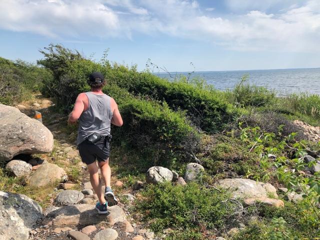 Niklas Bergh springer längs Skåneleden vid havet mellan Vejbystrand och Magnarp