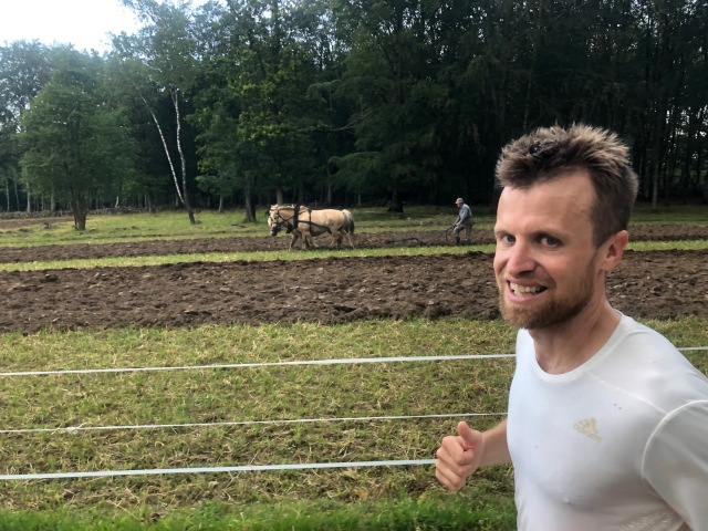 Fred Johansson i förgrunden, en bonde som plöjer åkern med hästar i bakgrunden. Zooma!