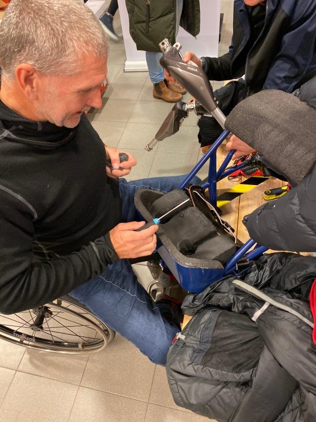 Anders Olsson modifierar sin sitski för att den ska passa Christoffer Lindhe
